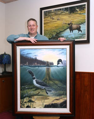 Sean Johnson showcases some of his artwork at his home in Nimishillen Township. Johnson won an Ohio Division of Wildlife art contest, and his painting will appear on the state duck stamp, which serves as a permit for water fowl hunting.