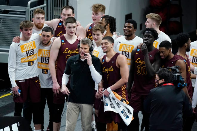 Loyola of Chicago players celebrate with head coach Porter Moser after beating Illinois in the second round of the NCAA tournament at Bankers Life Fieldhouse in Indianapolis on Sunday. Loyola upset Illinois 71-58.