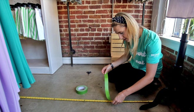Molly McKinney tapes off spaces for customers to stay six feet apart last year as businesses prepared to reopen after the governor's lockdown.