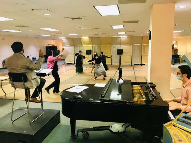 """Conductor Jesse Martins and stage director Martha Collins (in pink top) lead a rehearsal of Henry Purcell's """"Dido and Aeneas"""" opera at the Sarasota Opera House."""