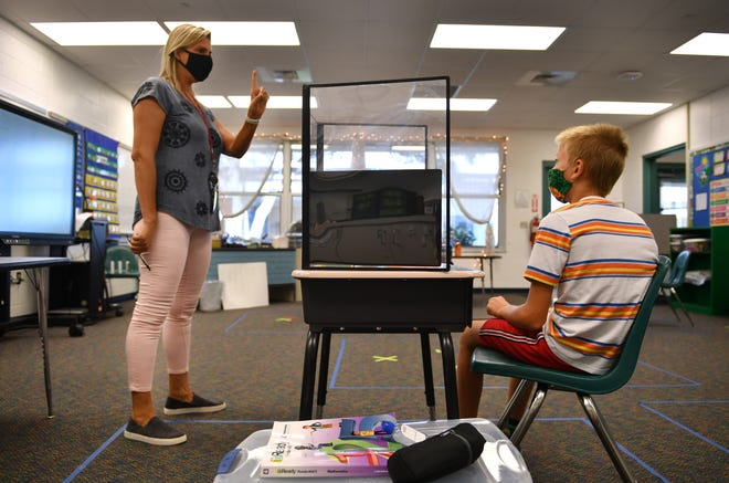 Teacher Lynn Hagan helps fourth grade student Daye Miller with a spelling lesson at Oak Park School in October. Sarasota County Schools have seen a spike in COVID-19 cases in the aftermath of spring break.