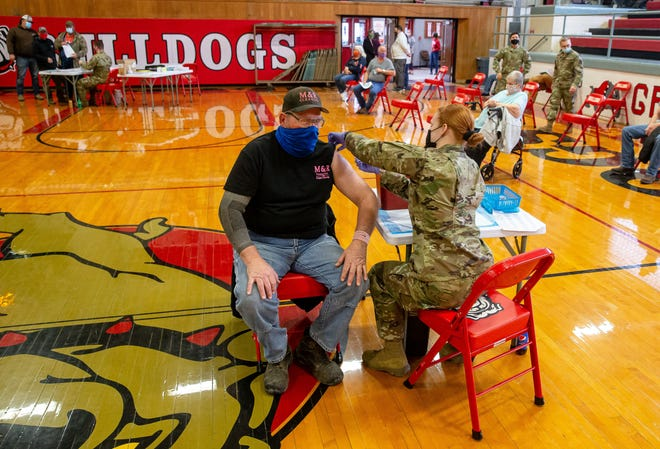 Richard Kauzlarich, of Easton, receives his dose of the Johnson & Johnson COVID-19 vaccine from Army National Guard Sgt. Reilly Gallagher in the gymnasium of the Greenview High School in Greenview on Friday. Greenview Community Unit School District 200 partnered with the Menard and Sangamon County Health Departments and the Illinois National Guard to provide the COVID-19 vaccine to more than 400 members of their community. [Justin L. Fowler/The State Journal-Register]