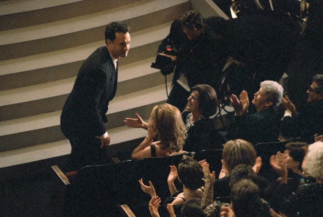 """Tom Hanks acknowledges his wife, Rita Wilson, as he leaves his seat in the Shrine Auditorium, March 27, 1995, to accept his Oscar for best actor for his role in """"Forrest Gump"""" at the 67th Annual Academy Awards in Los Angeles."""