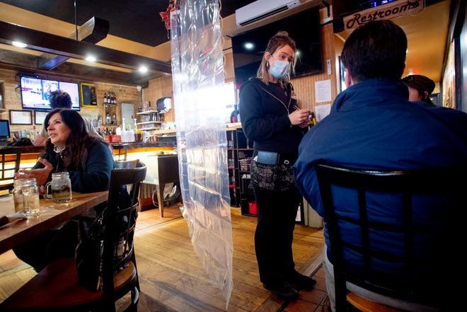 FILE - In this Nov. 24, 2020, file photo, waitress Rikkie Schleben takes down lunch orders from Tabitha Kemble, right, and her father Ken Kemble for dine-in service at Woodchips BBQ in Lapeer, Mich. Michigan, which not long ago had one of the country's lowest COVID-19 infection rates, is confronting an alarming spike that some experts worry could be a harbinger nationally. In what public health authorities across the U.S. have been warning for months might happen around the country, the resurgence is being fueled by loosened restrictions, a more infectious variant and pandemic fatigue.  (Jake May/The Flint Journal via AP, File)