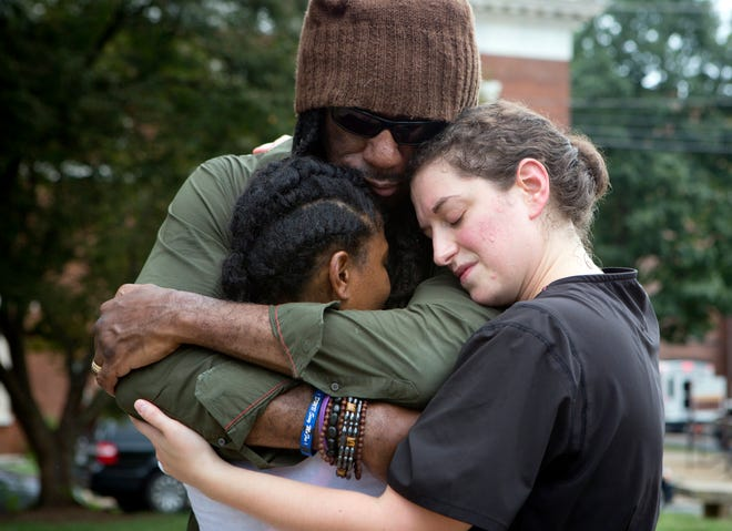 """FILE - This photo from Tuesday Aug. 15, 2017, shows Aaliyah Jones, 38, left, Boyd Tinsley of the Dave Matthews Band, center, and Amy Hastings, 29, right, as they embrace each other near the Confederate General Robert E. Lee monument in Emancipation Park, Charlottesville, Va., following a deadly white nationalists rally over the weekend. In a nation founded on whiteness, experts share perspective on whether it can be discussed. If white people want the future to be different, said Rev. Susan Chorley, a Boston area pastor, they have to be willing to look at the past and the present. """"I think it's on us,"""" she said. (AP Photo/Julia Rendleman, File)"""