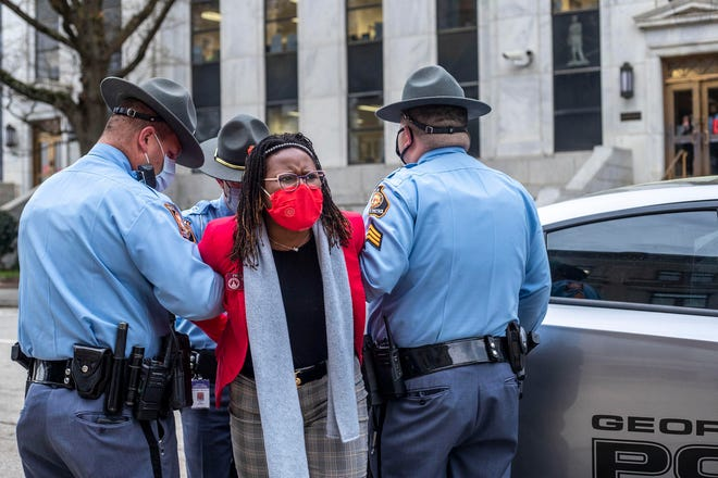 State Rep. Park Cannon, D-Atlanta, is placed into a patrol car by Georgia state troopers after she was arrested March 25 at the Georgia Capitol, in Atlanta. Cannon was arrested after she attempted to knock on the door of Gov. Brian Kemp's office after he signed into law a Republican-sponsored overhaul of state elections.