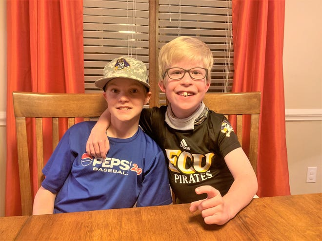 East Carolina baseball fans and brothers Joyner, left, and Reid, right, pose for a photo at the Haddock's dining room table.