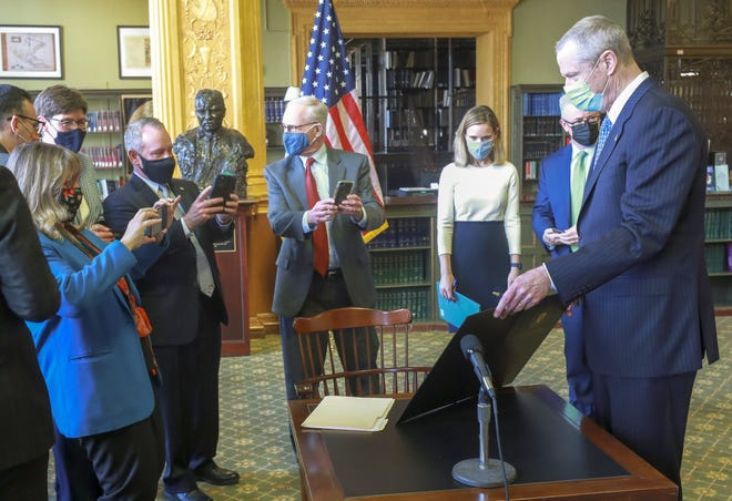 Gov. Charlie Baker holds up the state's new climate policy legislation he signed Friday at the State House in Boston.