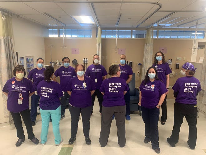 """Non-striking nurses at St. Vincent Hospital with T-shirts that say """"Supporting Colleagues Above Bullying,"""" a positive variation of the word """"scab."""""""