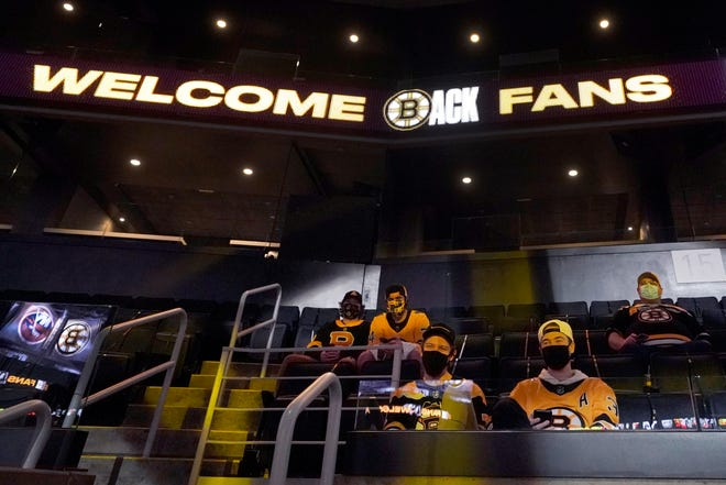Bruins fans sit in socially distanced groups in TD Garden seats before Thursday's game. This is the first Bruins home game of the season which fans were allowed, in limited numbers, to attend.