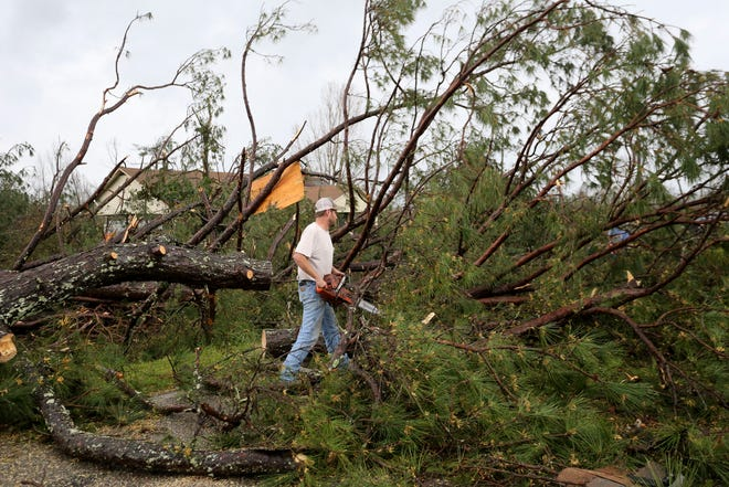 Volunteers clear fallen trees from the road after a tornado touched down near Centreville, Alabama, on Thursday, March 25, 2021.