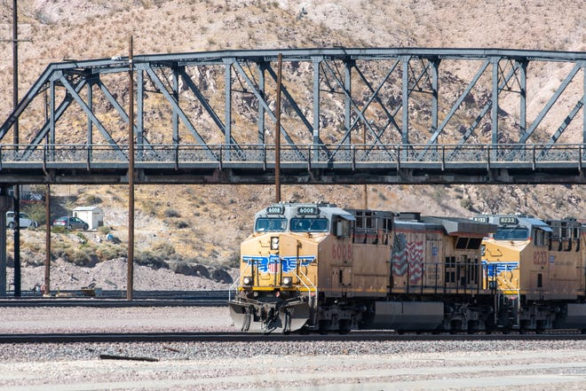 A train passes underneath the First Avenue Bridge in Barstow in March 2020.