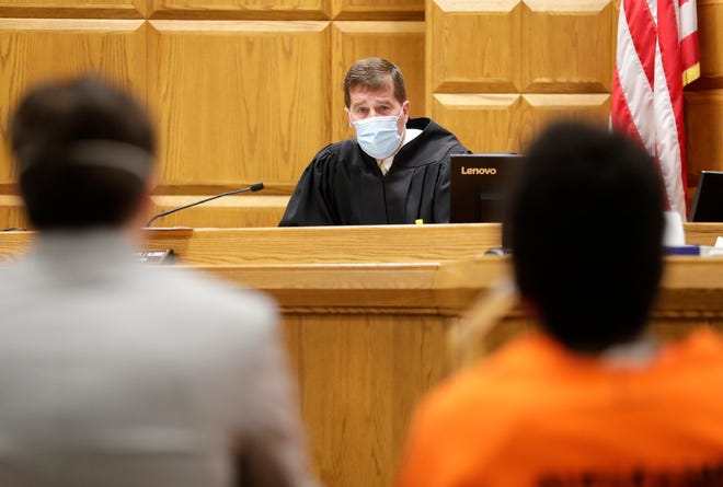 Wearing a mask, Outagamie Circuit Judge Mark McGinnis holds court Friday in Appleton.