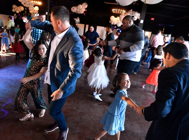 Fathers and their children twirl during Thursday's Daddy Daughter Dance at Station 1 Venue.
