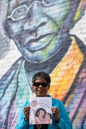 """Barbara M. Allen poses for a picture under the Sojourner Truth mural on Friday, March 26, 2021 in Battle Creek, Mich. Allen is a sixth-generation granddaughter of Sojourner Truth, she recently wrote a children's book titled """"Remembering Great Grandma."""""""
