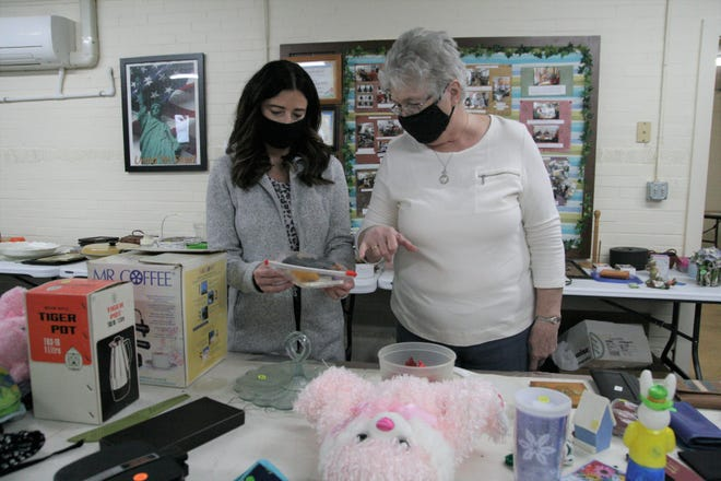 Jenni Leuthold, left, and Carolyn Rogers of the Galion Golden Age Center look over items they were selling during the recent rummage and bake sale.