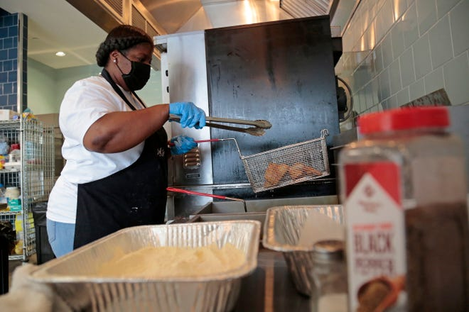 Candice Holloway, owner of Soul Secrets catering service, pulls an order of fried fish from the deep fryer for a weekly fish fry at Findlay Kitchen in the Over-the-Rhine neighborhood of Cincinnati on Friday, March 26, 2021.
