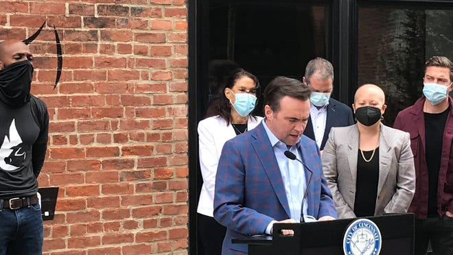 Just Q'in barbecue restaurant owner Matthew Cuff is at left as Cincinnati Mayor John Cranley unveils a new $4 million stimulus program for bars and restaurants in the Walnut Hills restaurant's courtyard as other city officials and restaurant owners watch at right.