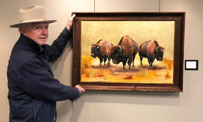 """Henderson native and accomplished amateur artist Bill Burton picks up his painting, """"Kentucky Bison LBL,"""" following an exhibition at the Audubon State Park museum. Burton donated the piece to Lake Barkley State Resort Park, where it today hangs in the lobby of the park's lodge."""