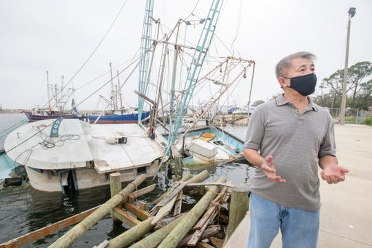 Linh Tran talks March 25 about his fishing boat, which remains submerged behind Joe Patti's Seafood in Pensacola.
