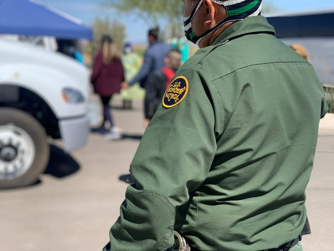 A border agent watches on as a group of 13 asylum seekers exit a Border Patrol bus on March 17, 2021. The group of migrants will be tested for COVID-19 before they are transported to a migrant shelter in California.