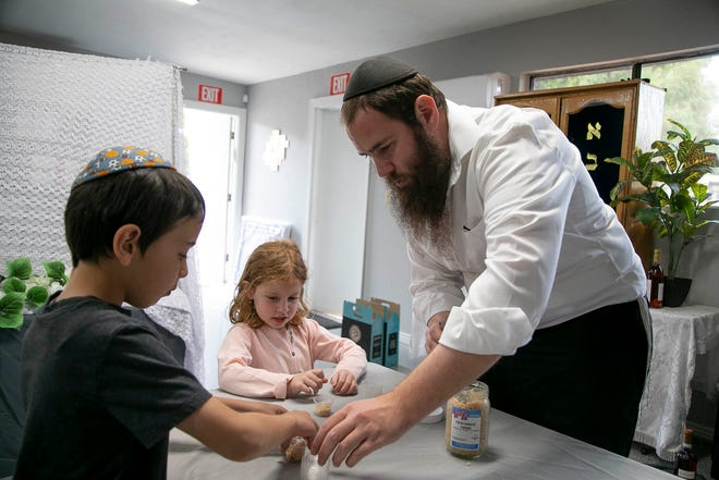Rabbi Shlomo Levertov and his children fill small plastic containers of Maror for the Seder 2 Go kits at their home on March 25, 2021.