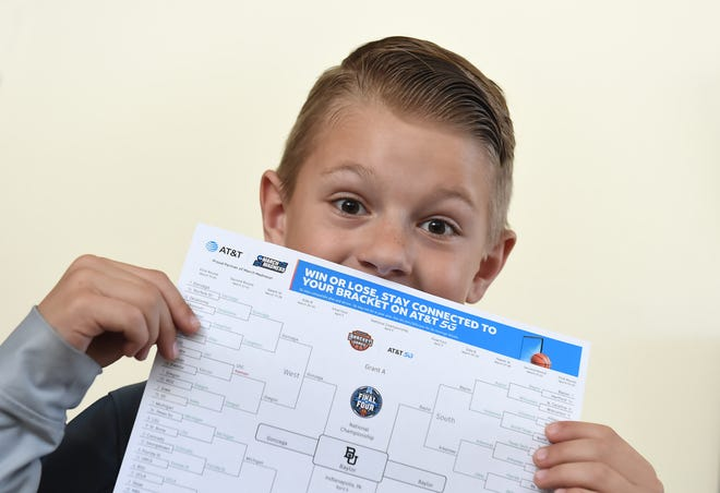 Grant Anderson, 9, holds up March Madness mens basketball bracket in his Reno Home on March 26,202. Grant has has gotten only one wrong.