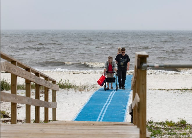 Barbara Davis, left, makes her way back to the parking lot while pushing her walker on a Mobi-mat that was recently laid out on the beach in Carrabelle, Florida. The blue mat makes the beach more accessible for those with disabilities, walkers, and parents with strollers.