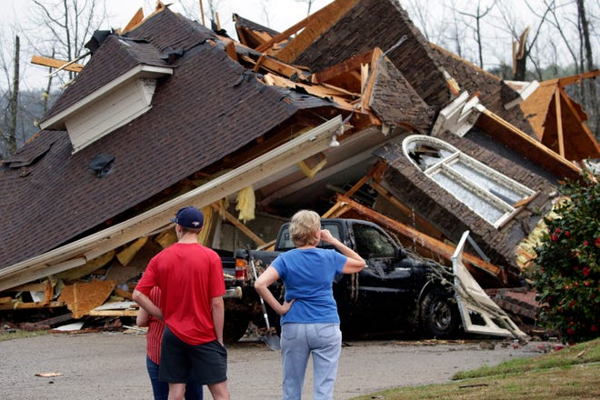 Residents survey damage to homes after a tornado touched down south of Birmingham, Alabama, in the Eagle Point community on Thursday, March 25, 2021.