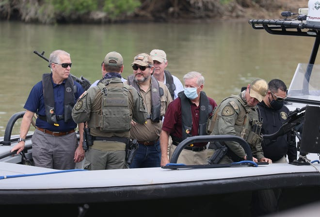 Sen. Ted Cruz, R-Texas, and Sen. Lindsey Graham, R-S.C., stand aboard a Texas Department of Public Safety boat for a tour of part of the Rio Grande river on March 26 in Mission, Texas. The senators were part of a Senate delegation visiting the Texas-Mexican border.
