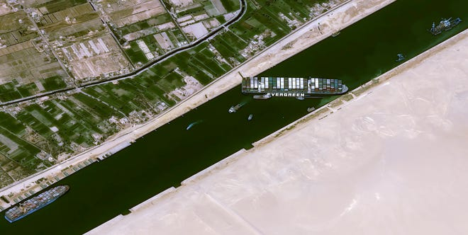 This satellite image from Cnes2021, Distribution Airbus DS, shows the cargo ship MV Ever Given stuck in the Suez Canal near Suez, Egypt, March 25, 2021. The skyscraper-sized cargo ship wedged across Egypt's Suez Canal further imperiled global shipping Thursday as at least 150 other vessels needing to pass through the crucial waterway idled waiting for the obstruction to clear, authorities said.
