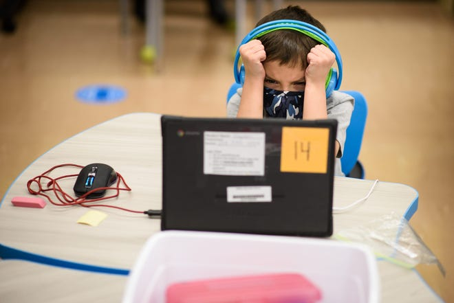 First grader Kayden Welch gets frustrated with his computer at Cliffdale Elementary School on Monday, March 15, 2021.