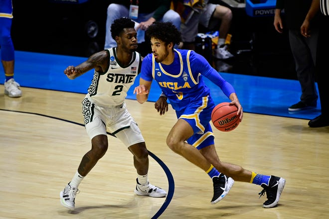 UCLA guard Johnny Juzang drives against Michigan State guard Rocket Watts (2) in the first half during the First Four of the 2021 NCAA Tournament at Mackey Arena.