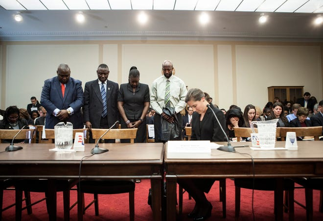 Lawyer Benjamin Crump stands with Sybrina Fulton and Tracy Martin, parents of Trayvon Martin, as they bow their heads for a moment of silence with Rebecca Monroe, right, then acting director of the Community Relations Service at the Justice Department, during a forum of Democratic members of the House Judiciary Committee, March 27, 2012.