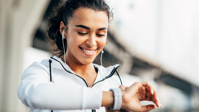 Smiling woman checking her physical activity on smartwatch. Young female athlete looking on activity tracker during training.