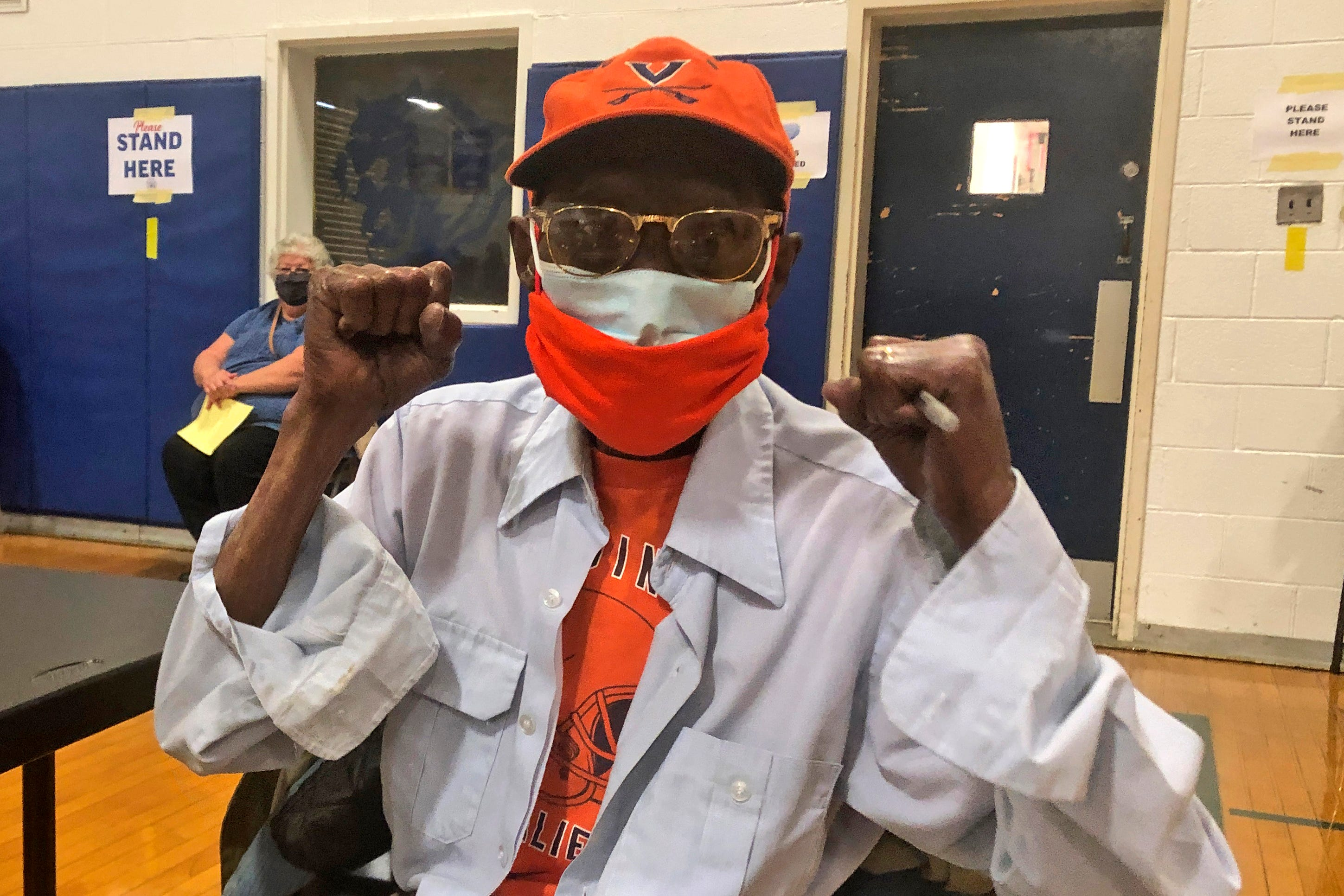 Charles Robbins celebrates getting his second shot of coronavirus vaccine at Surry County High School in Dendron, Va., on Saturday, Feb. 27, 2021.