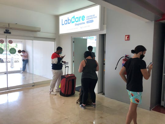Travelers wait in line for a COVID test at Cancun International Airport.