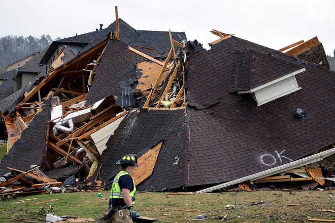 A firefighter surveys damage to a house after a tornado touches down south of Birmingham in the Eagle Point community damaging multiple homes Thursday March 25, 2021.