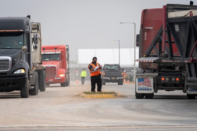 Trucks enter and leave a construction site to expand an existing facility to hold migrants on Wednesday, March 24, 2021, in Donna, Texas.
