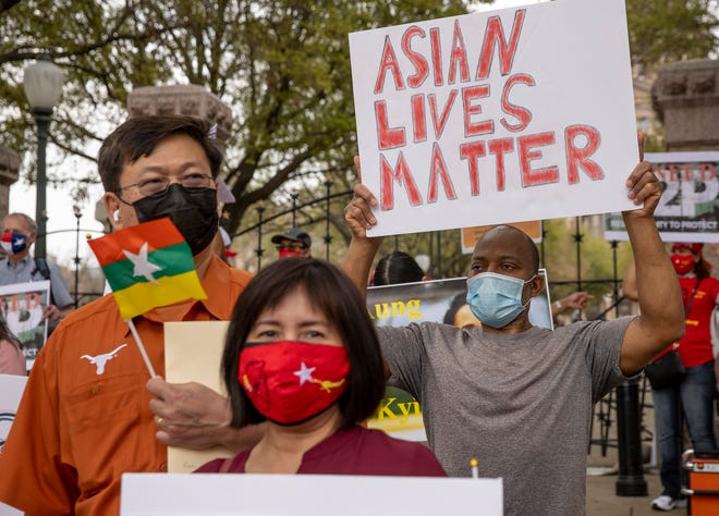 Derrick Wiley holds an 'Asian Lives Matter' sign during the protest Saturday.