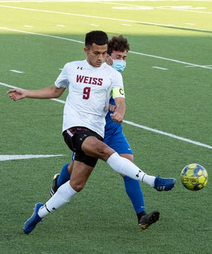 Weiss midfielder Cesar Rodriguez passes the ball downfield as McCallum's Felipe Perez defends in a Class 5A bidistrict playoff at House Park on Friday. Rodriguez had two goals as Weiss won 4-0.