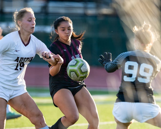 Round Rock's Alycia Buenaventura, center, tries to get past Austin High keeper Erin Stansbury, right, and defender Audrey Grace Davis during Round Rock's 7-1 win over Austin High in a Class 6A bdistrict girls playoff soccer match at Dragon Stadium on Friday.