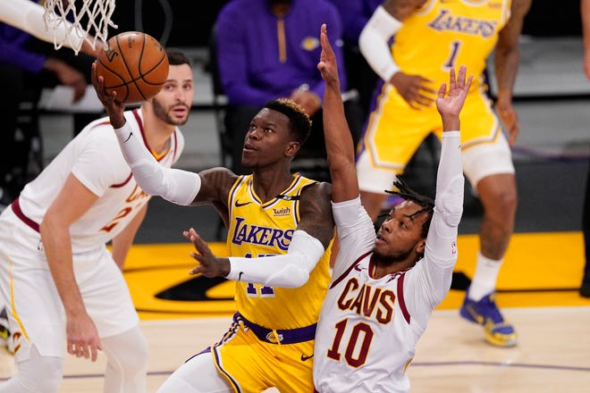 Los Angeles Lakers guard Dennis Schroder, center, shoots as Cleveland Cavaliers guard Darius Garland, right, defends and forward Larry Nance Jr. watches during the first half of an NBA basketball game Friday, March 26, 2021, in Los Angeles. (AP Photo/Mark J. Terrill)