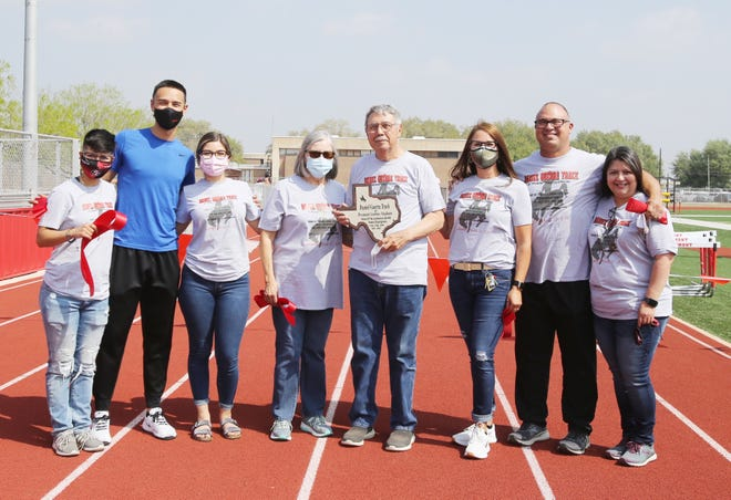 Coach Daniel Guerra stands with his family accepted a plaque during the naming of Premont's track. The track was named in his honor.