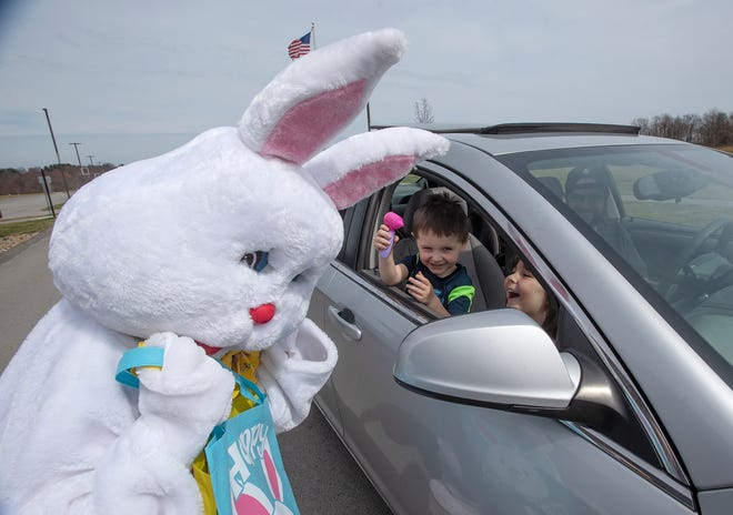 Carter, 3, and Jordyn, 5, Zimmerman, of Patterson Township, laugh after pretending to check the Easter Bunny's ears with a toy otoscope Saturday during a drive-thru Easter event at Wright Field in Chippewa Township.