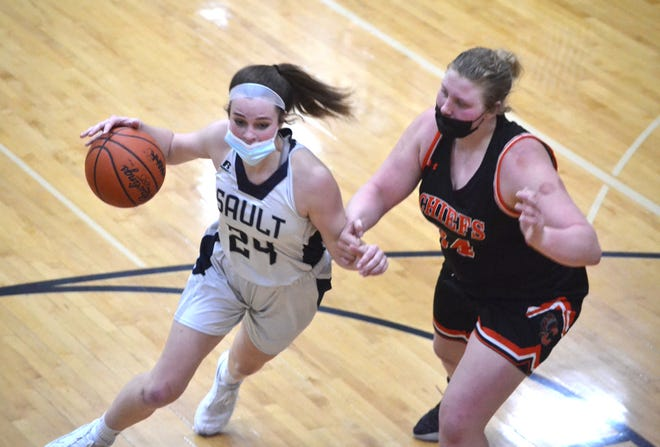 Sault Ste. Marie sophomore guard Claire Erickson (left) drives past Cheboygan senior center Isabelle Buhr during the first half of a Division 2 girls basketball district final in Cheboygan on Friday night.