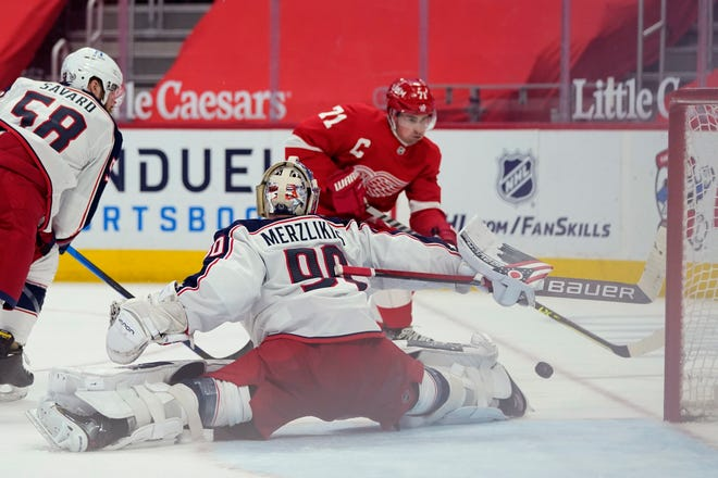 Elvis Merzlikins (90) deflects a shot by Detroit Red Wings center Dylan Larkin (71) in the second period Saturday at Little Caesar's Arena in Detroit.