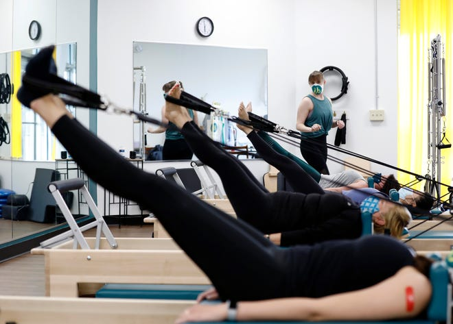 Heather Daye, right, teaches a fitness class at Studio 86 Fitness in Columbus, Ohio on March 26, 2021. Customers coming back to gyms now that the pandemic situation is improving.