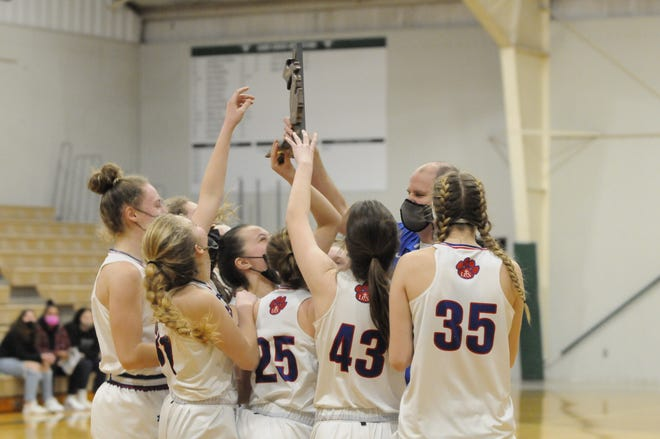Lenawee Christian head coach Jamie Salenbien hands the Division 3 district trophy to his team following Friday's win against Madison at Sand Creek.