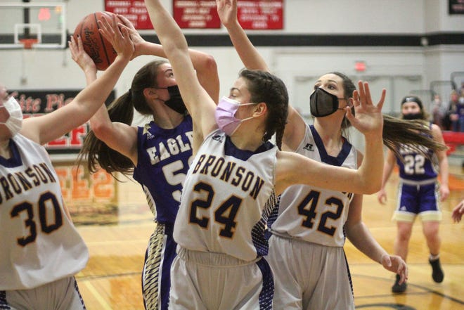 Bronson's Jenna Salek (24), Macy Covey (42) and Haylie Wilson (30) converge on Schoolcraft's Anna Schuppel in the paint Friday during the Division Three District finals